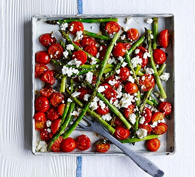 asparagus and tomatoes in pan on white table