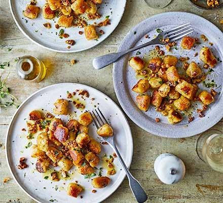 3 plates serving parsnip gnocchi, garnished with walnut crumbs