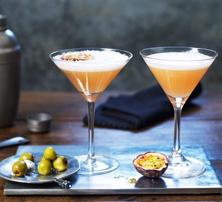 Passion fruit cocktails in glasses with olives and halved fruit