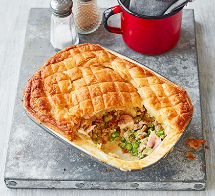 Pea & ham pot pie served in a pie dish with cutlery alongside
