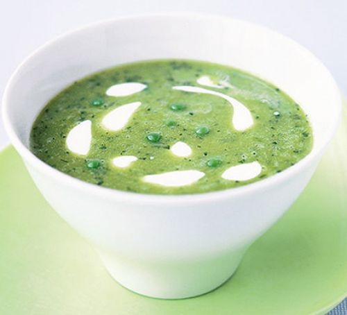 Bowl of pea and mint soup topped with creme fraiche swirls