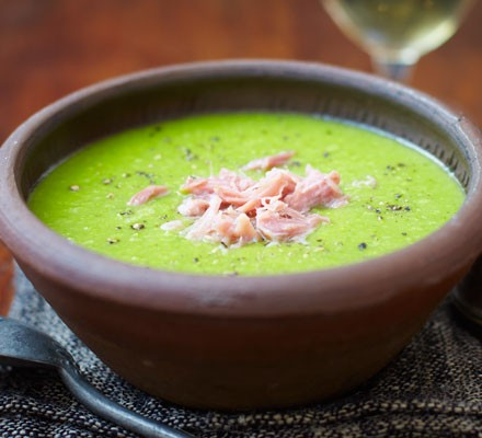 Pea and ham soup in bowl with spoon
