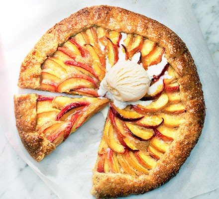 Peach galette with brown sugar crust cut into slices