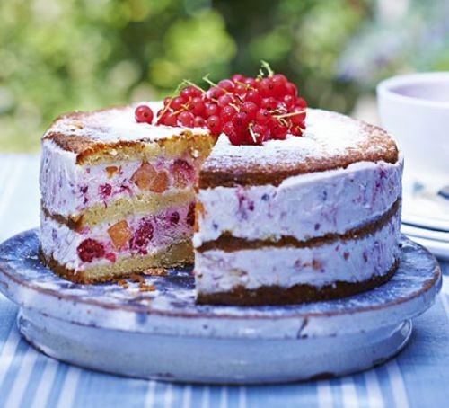Peach & red berry ice cream cake, on a serving platter, in a garden