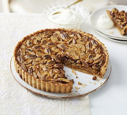 New England pecan pie with a slice taken out, served on a plate