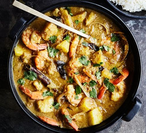 Prawn and pineapple curry in a pot with spoon