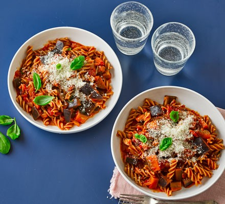 Two bowls of pasta arrabbiata with aubergine and cheese