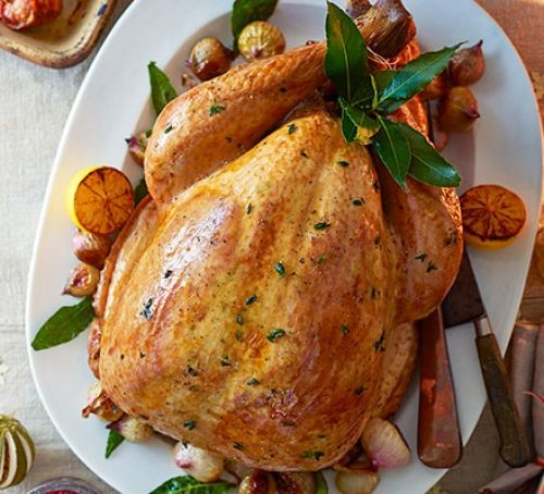 Whole turkey surrounded by citrus fruit and bay leaves