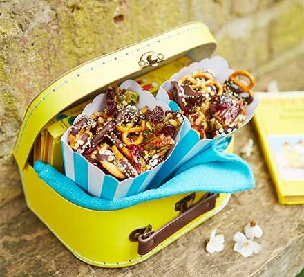 A small yellow lunchbox filled with picnic trail mix