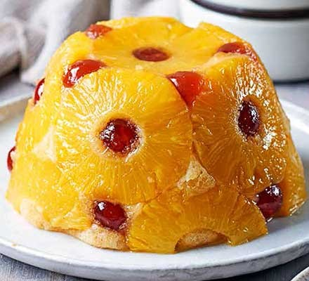 A plate serving pineapple & cherry sponge with coconut rum custard