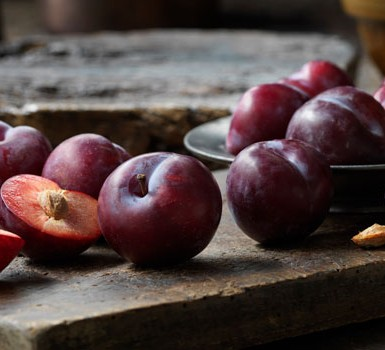 Plums cut in half on table