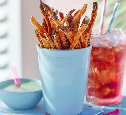 A blue pot containing polenta sweet potato fries with a herb dip on the side