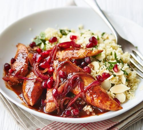 Chicken pieces in pomegranate sauce with couscous in a bowl
