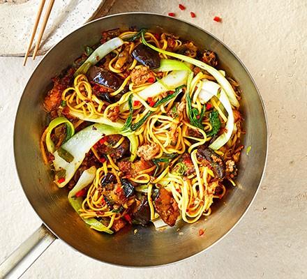 Pork & aubergine noodle stir-fry served in a wok