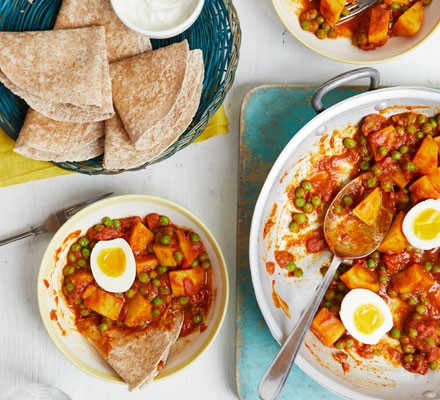Pea, potato and egg curry in bowls with flatbreads