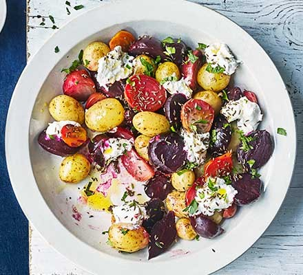 Potatoes & beets with curd, caraway & flaxseed oil served on a plate
