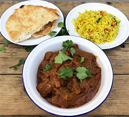 Pressure cooker beef curry served with rice and naan bread