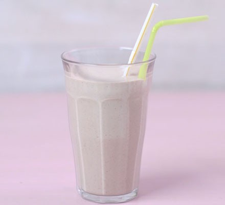 A glass of homemade protein shake with two straws