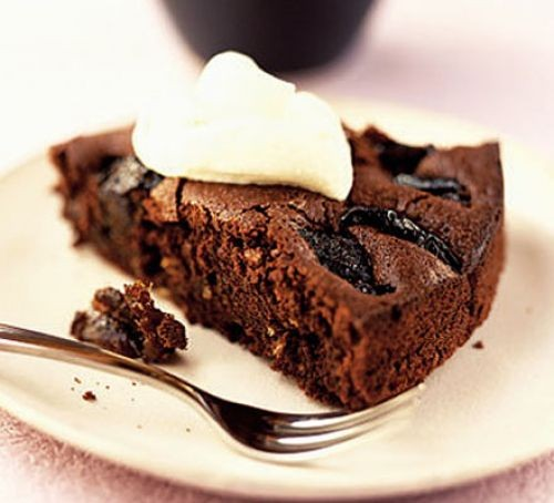 Prune and chocolate torte slice topped with cream