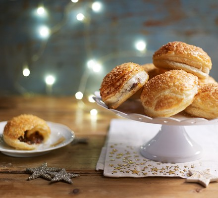 Puff pastry mince pies on a cake stand and one on a plate with a bite taken out