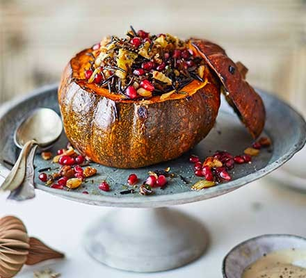 Stuffed pumpkin on a silver serving stand garnished with pomegranate seeds