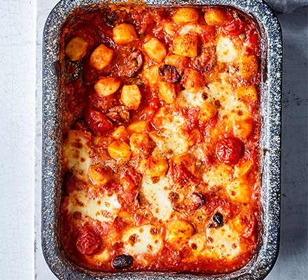 Puttanesca baked gnocchi served in a casserole dish