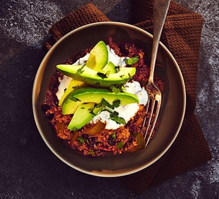 Quinoa chilli with avocado & coriander served in a bowl