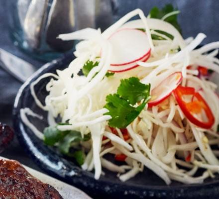White cabbage & radish slaw in a black bowl
