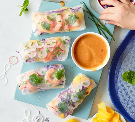 Rainbow rice paper rolls served on a chopping board