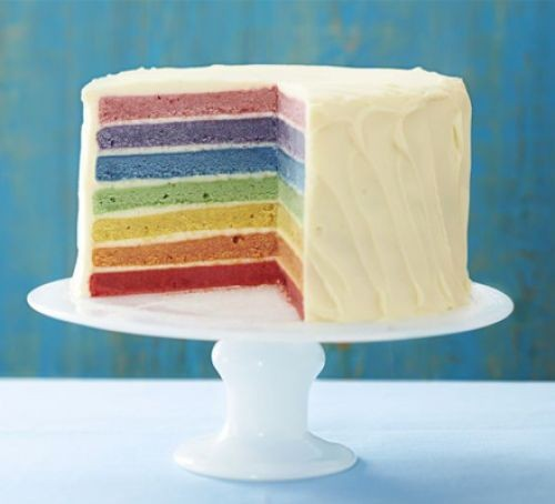 Multicoloured rainbow sponge cake with white frosting, on a stand