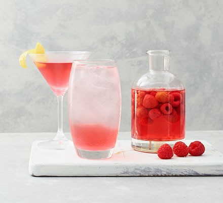 Raspberry gin served in a bottle with fresh raspberries