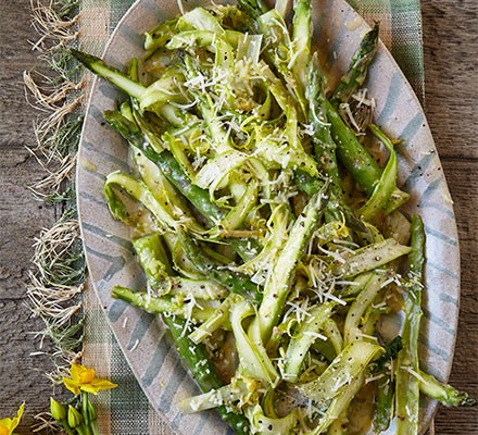 Raw & cooked asparagus with lemon & parmesan butter served in an oval dish