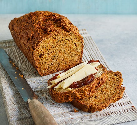 Honeyed carrot & thyme loaf cut into slices and served with cheddar and chutney