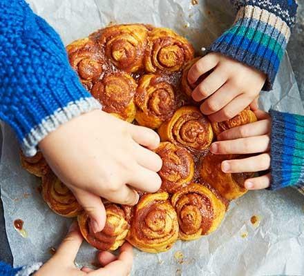 Children sharing cinnamon rolls