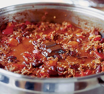 Chilli con carne cooking in a pan with chocolate melting on top