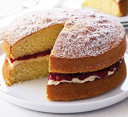 Victoria sponge cake on a plate with a slice cut out
