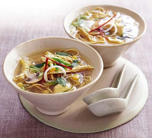 Chicken noodle soup in bowls with spoons