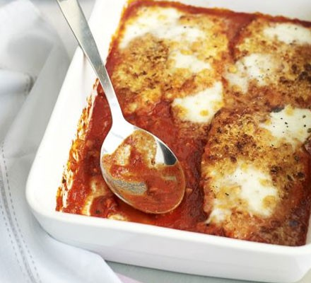 Chicken parmigiana in a large oven dish with serving spoon