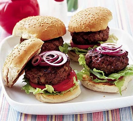 Four beef burgers on a plate