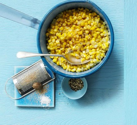 Creamed corn in a pan with spoon and grater on the side
