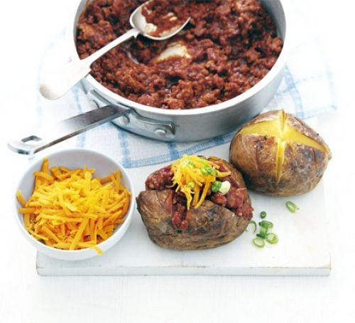 Baked potatoes filled with turkey chilli and grated cheese