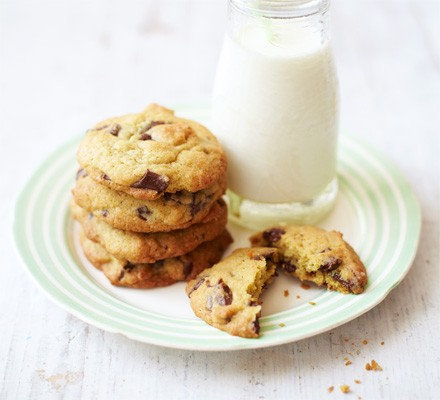 Chocolate chip cookies on a plate with a small glass bottle of milk