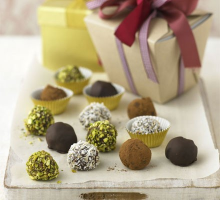 Chocolate truffles with coloured coatings by a gift box