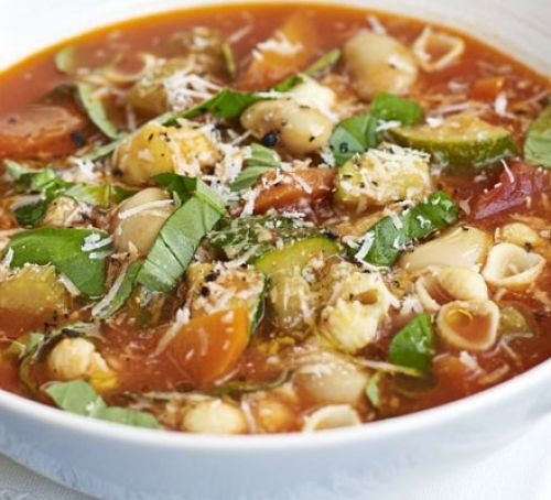 Italian vegetable soup in a bowl with pasta and basil