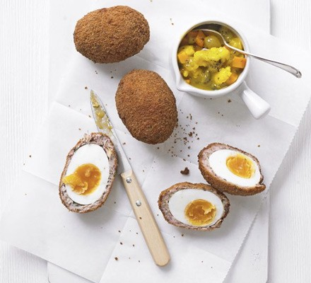 Scotch eggs on a table with pickle