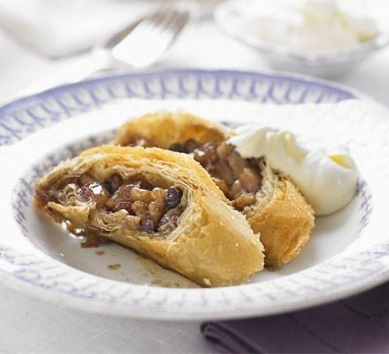 Caramelised apple & walnut strudel with cream on plate