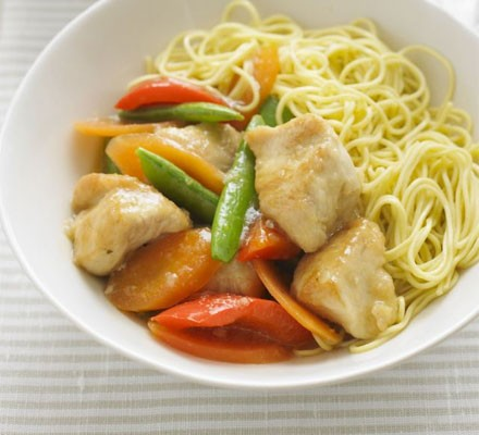 Bowl of lemon chicken chunks with vegetables and noodles