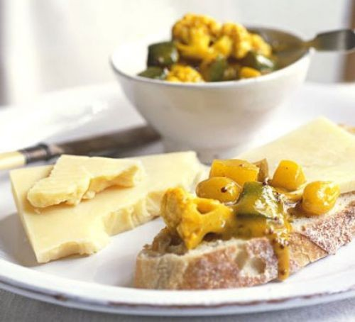 Piccalilli in a bowl and on bread with cheese