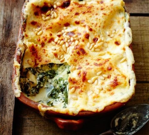 Spinach and pine nut lasagne in a baking dish with a scoop taken out