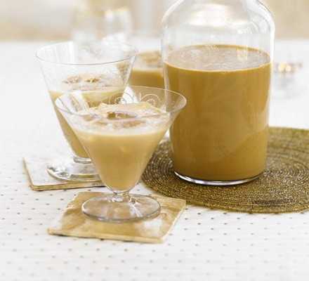 Irish cream liqueur in bottle and in glasses with ice
